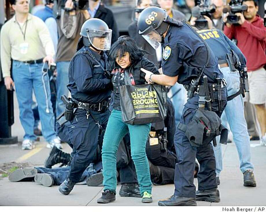 Police arrest a demonstrator in Oakland, Calif., on Friday, Jan. 30, 2009, during a protest in support of Oscar Grant, an unarmed 22-year-old killed by BART transit police. About 100 demonstrators took to the streets in reaction to a $3 million dollar bond set for Officer Johannes Mehserle who is charged in the New Year's Day killing. (AP Photo/Noah Berger) Photo: Noah Berger, AP