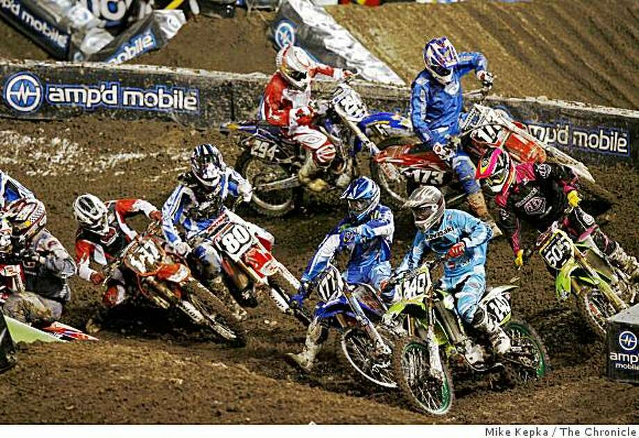 A crash around the second corner during the start of the supercross lites division. Super cross comes the AT&T Stadium Saturday, 1/27/07. Photo: Mike Kepka, The Chronicle