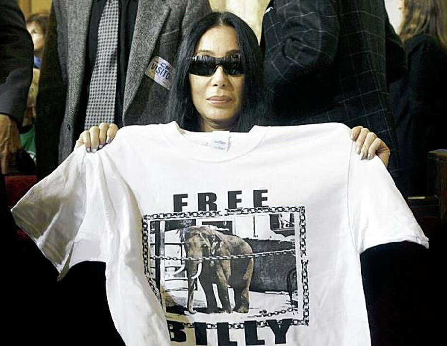 """Actress Cher holds a """"Free Billy""""  t-shirt Wednesday Jan. 28, 2009 at the Los Angeles City Council chambers to urge scapping construction plans on the Los Angeles Zoo's $42 million elephant exhibit, in Los Angeles. The City Council voted Wednesday to finish the elephant exhibit and keep its lone pachyderm Billy at the zoo, despite pleas by celebrity opponents to scrap the project.  (AP Photo/Nick Ut) Photo: Nick Ut, AP"""