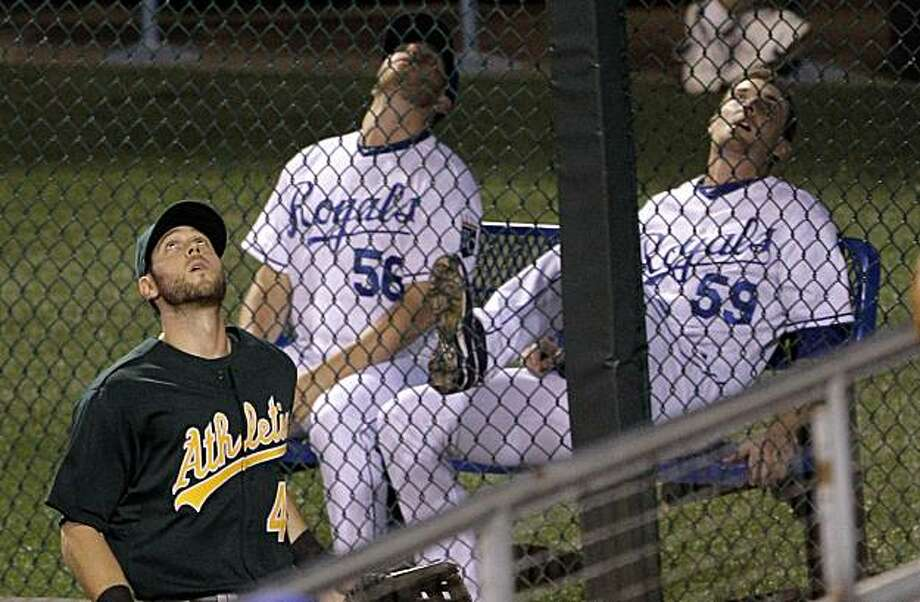 Oakland Athletics left fielder Jeremy Hermida along with Kansas City Royals pitchers in the bullpen Greg Holland (56) and Philip Humber (59) look to the sky for a two-run home run hit by Kansas City Royals' Wilson Betemit during the third inning of a baseball game Tuesday, Sept. 14, 2010. Photo: Charlie Riedel, AP