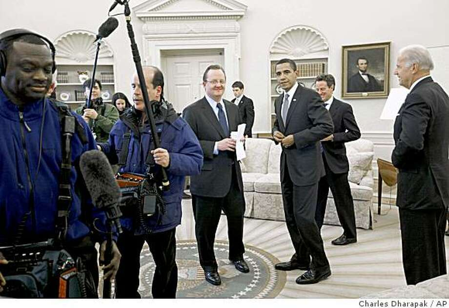 Television sound engineers leave the Oval Office at the White House after President Barack Obama spoke with reporters at the end of his meeting with Treasury Secretary Tim Geithner, second right, and Vice President Joe Biden, right, Thursday, Jan. 29, 2009, in Washington. Also pictured is White House Press Secretary Robert Gibbs, center. (AP Photo/Charles Dharapak) Photo: Charles Dharapak, AP