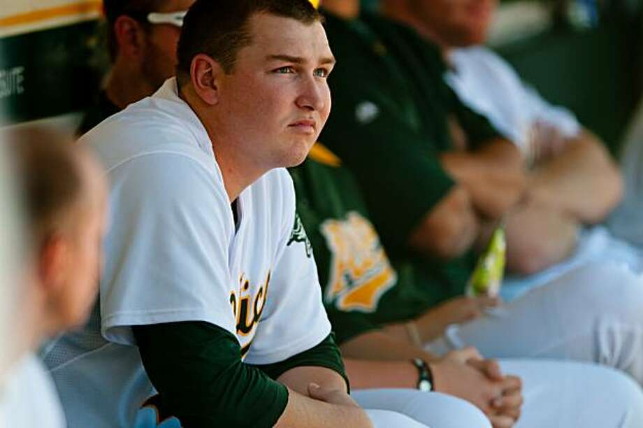 Trevor Cahill rests in the A's dugout between innings in Oakland on Saturday. Photo: Chad Ziemendorf, The Chronicle