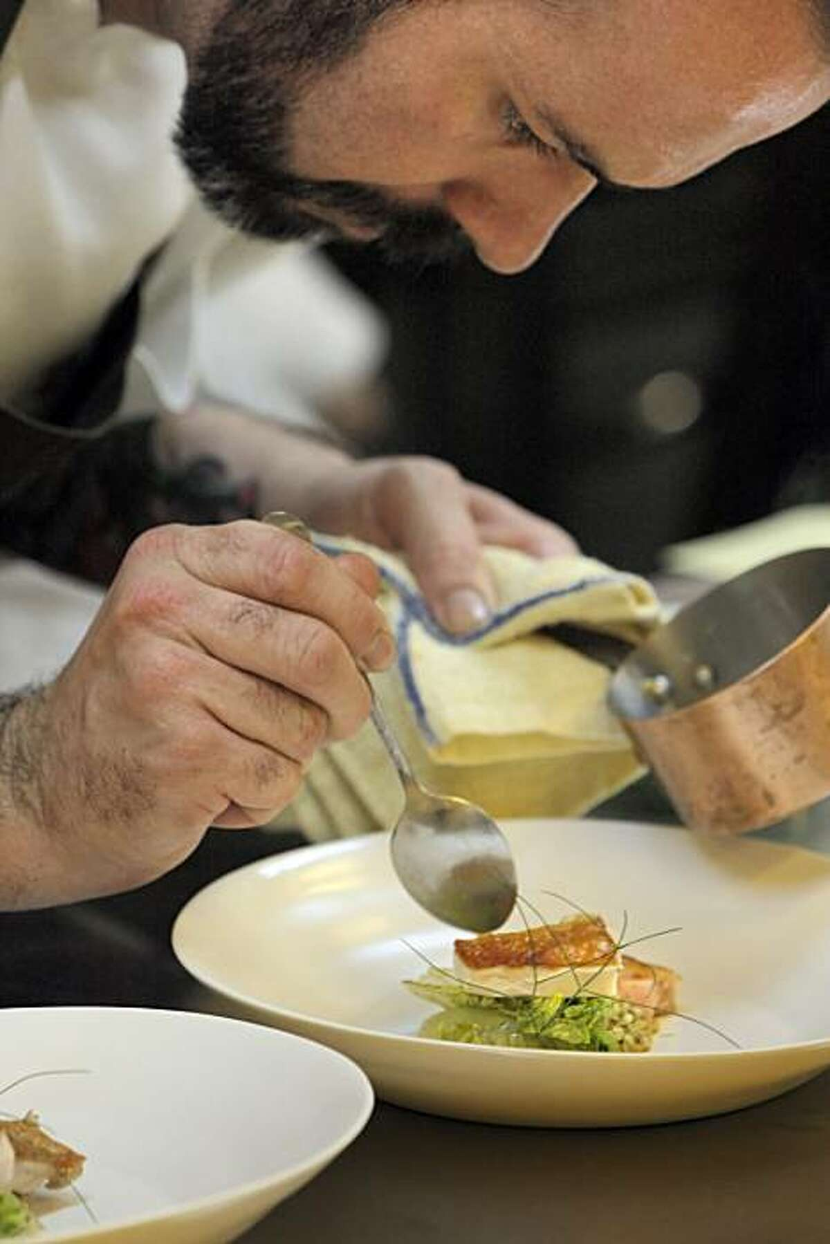 Sous chef Nick Ecker, finishes a dish before it is taken to a guest during dinner at Coi Restaurant in San Francisco, Calif., on Thursday, August 26, 2010. Executive Chef Daniel Patterson uses molecular gastronomy focusing on local food to create visually stunning, and delicious dishes