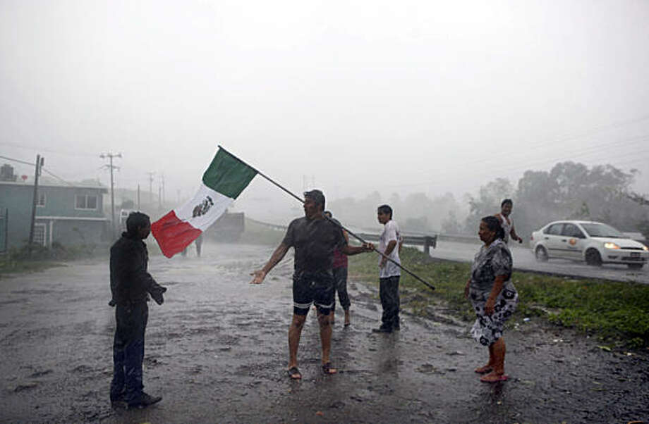 People, one carrying a Mexican flag, speak under pouring rain due to Hurricane Karl in Cardel, some 35 km, about 22 miles, of Veracruz,  Mexico, Friday, Sept. 17, 2010. Hurricane Karl hit Gulf Coast near Veracruz with winds of 115 mph, some 185 kph. Photo: Alexandre Meneghini, AP