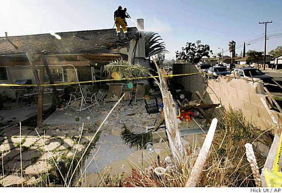 San Bernardino County firefighters douse flames on the roof of a home Thursday, Jan. 29, 2009, where a car crashed into the home killing the three young occupants of the car in Fontana, Calif. Three boys were killed when they fled from police in a car that then flipped over a wall and ended up in the yard of this Fontana home, authorities said Thursday. (AP Photo/Nick Ut) Photo: Nick Ut, AP