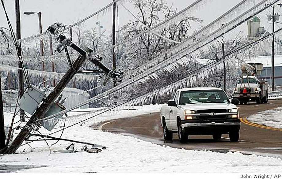 A pair of vehicles prepare to pass the top of a power pole that fell onto the sidewalk along 3rd Street in Paducah, Ky. on Saturday, Jan. 31, 2009. (AP Photo/The Paducah Sun, John Wright) Photo: John Wright, AP