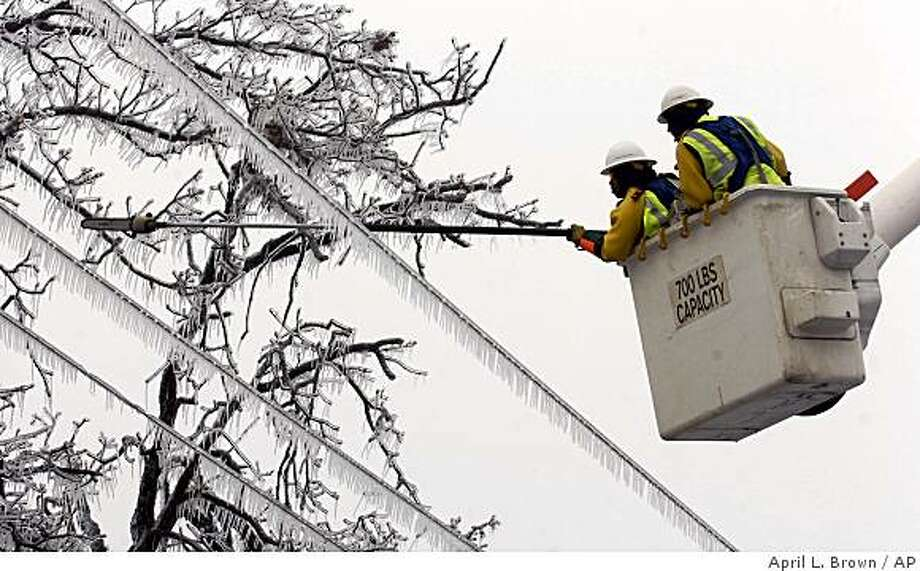 A line crew with Southwestern Electric Power Company saws off limbs that are hanging across power lines in Fayetteville, Ark., Thursday, Jan. 29, 2009. Thousands in the city are still without electricity following an ice storm that hit the northwest Arkansas region Tuesday.  (AP Photo/April L. Brown) Photo: April L. Brown, AP