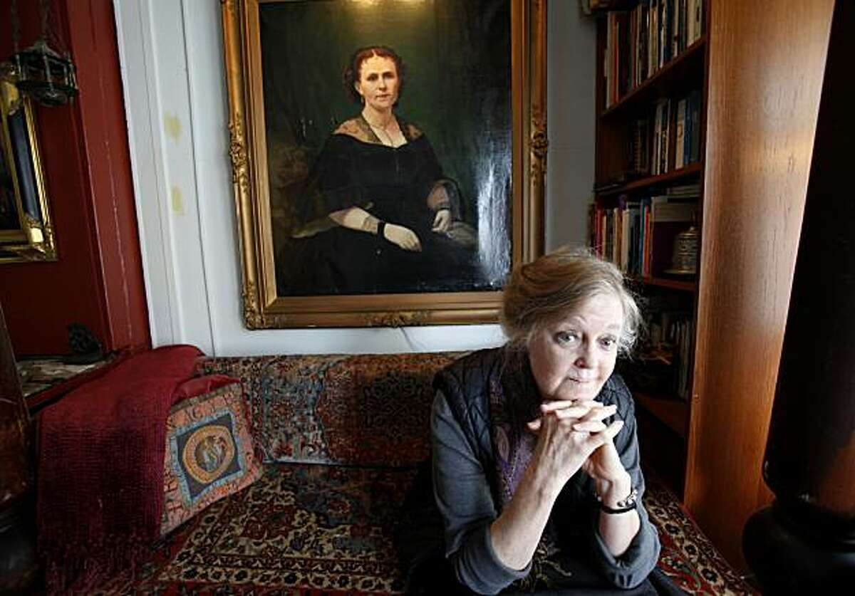 Maya Cain sits in the living room of her apartment below a portrait of a relative. Maya Cain believes her