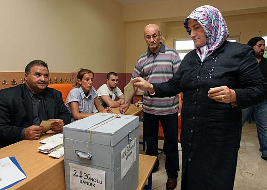 A Turkish woman casts her vote in a referendum on changes to the constitution that was crafted in the wake of Turkey's 1980 military coup, in Istanbul, Turkey, Sunday, Sept. 12, 2010. Turks voted Sunday on whether to amend a military-era constitution in what the government says is a key step toward EU-style democracy, despite opposition claims that the proposed reforms would shackle the independence of the courts. Photo: Burhan Ozbilici, Associated Press
