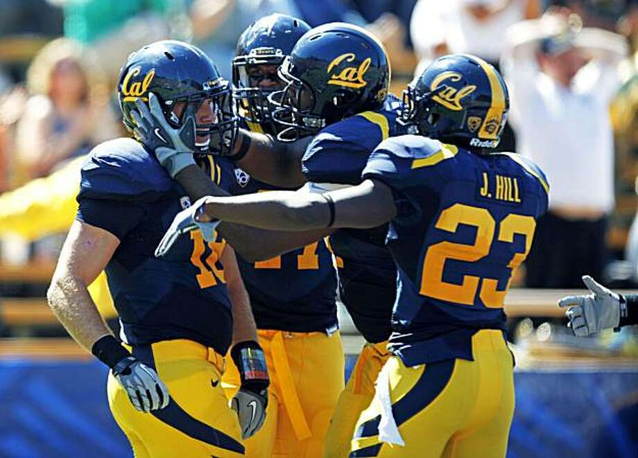 Cal's Mike Mohamed (18) left is greeted by his teammates after scoring a touchdown on an interception off Colorado quarterback Tyler Hansen  in the second quarter in Berkeley on Saturday. Photo: Lance Iversen, The Chronicle