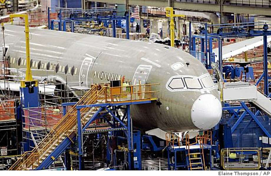 One of the first Boeing 787 jets is seen on the assembly line nearly surrounded by scaffolding during a media tour May 19, 2008, in Everett, Wash. The Boeing Co. announced plans to cut 10,000 jobs after reporting a surprise fourth-quarter loss Wednesday, Jan. 28, 2009. (AP Photo/Elaine Thompson, File) Photo: Elaine Thompson, AP