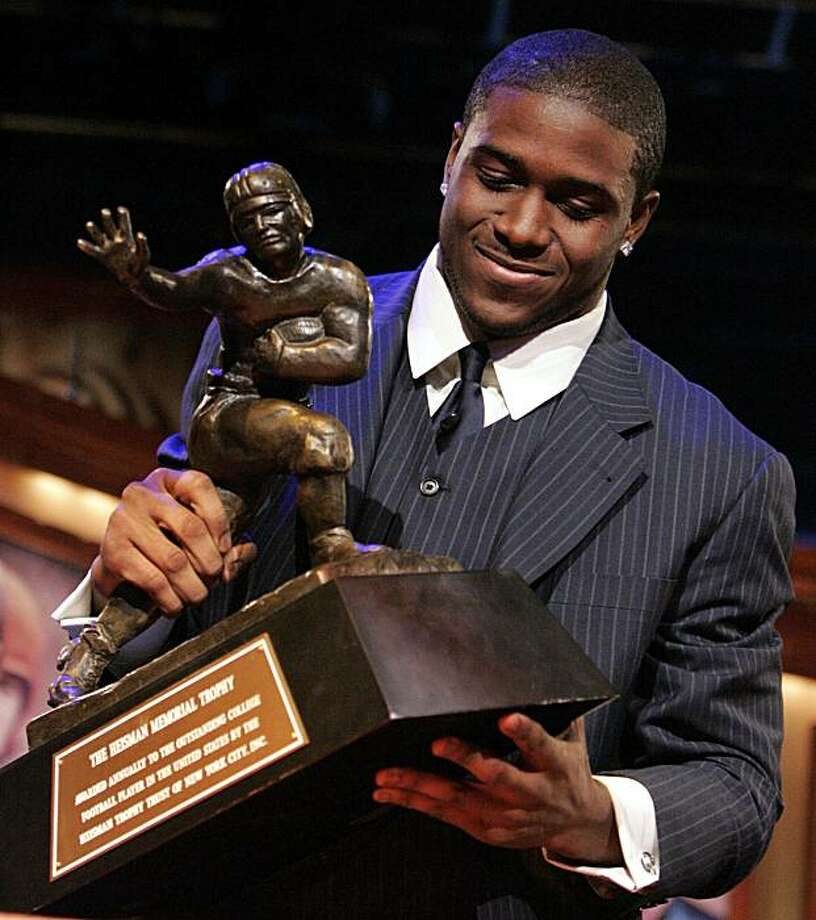 In this Dec. 10, 2005, file photo,  Southern California tailback Reggie Bush picks up the Heisman Trophy after being announced as the winner of the award in New York. Bush said Tuesday, Tuesday, Sept. 14, 2010, that he is forfeiting his Heisman Trophy. Photo: Julie Jacobson, AP