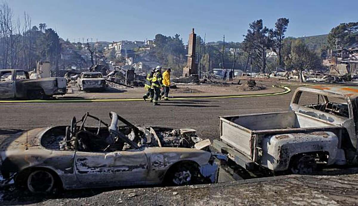 Firefighters walk along the burnt out homes, Friday Sept. 10, 2010,in the San Bruno neighborhood that was an inferno last night, in San Bruno, Calif.