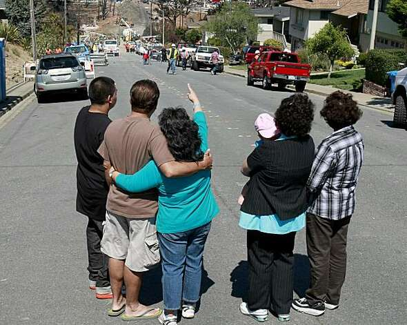 The Vides family looks down Glenview Drive in San Bruno after arriving home to find their home still intact Sunday. Photo: Brant Ward, The Chronicle