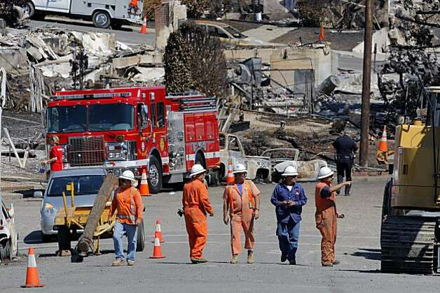 Utility crews walk through the closed section of the Glenview area of San Bruno as some of the people evacuated return to their neighborhood Sunday. Photo: Carlos Avila Gonzalez, The Chronicle