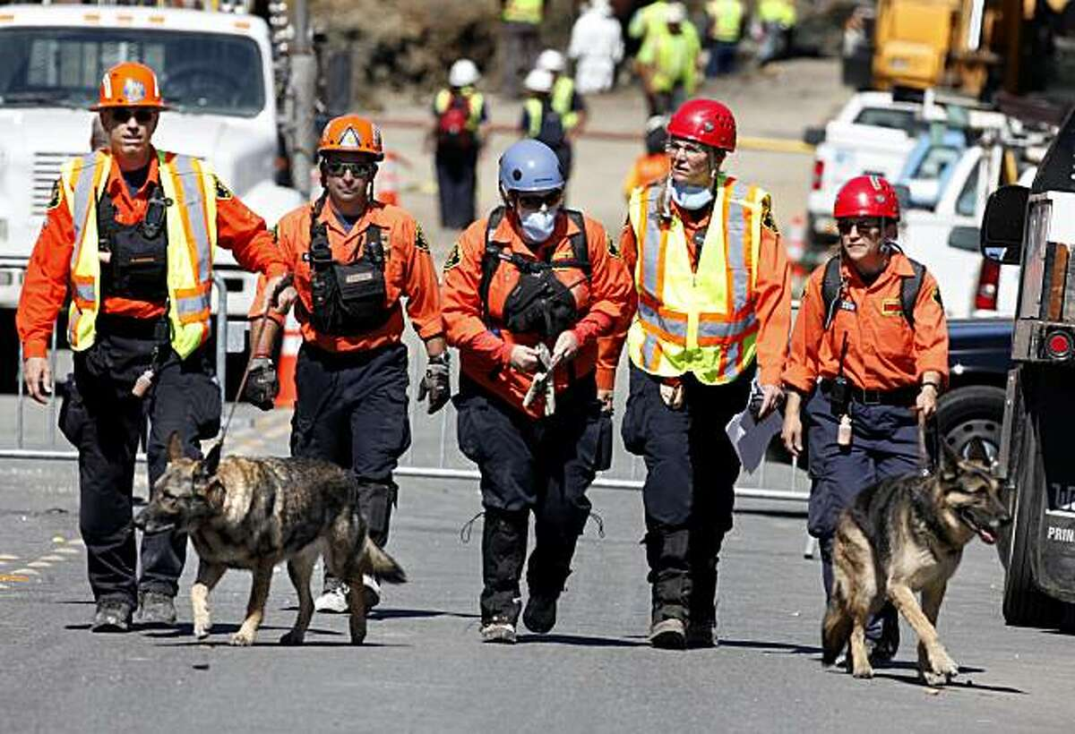 Alameda County Search and Rescue officials and their dogs leave the blast scene in San Bruno on Sunday.