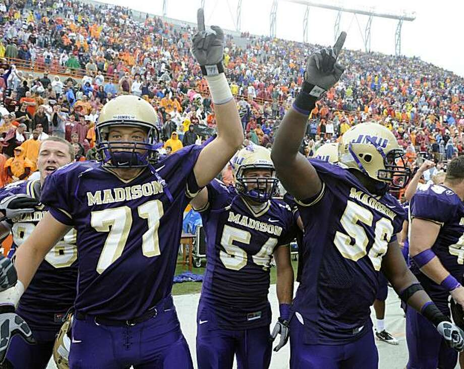 James Madison players, from left, Josh Wells, Chad Byers, and Jordon Stanton celebrate after defeating 13th ranked Virginia Tech 21-16 in a NCAA football game at Lane Stadium in Blacksburg, Va., Saturday, Sept. 11, 2010. Photo: Don Petersen, AP