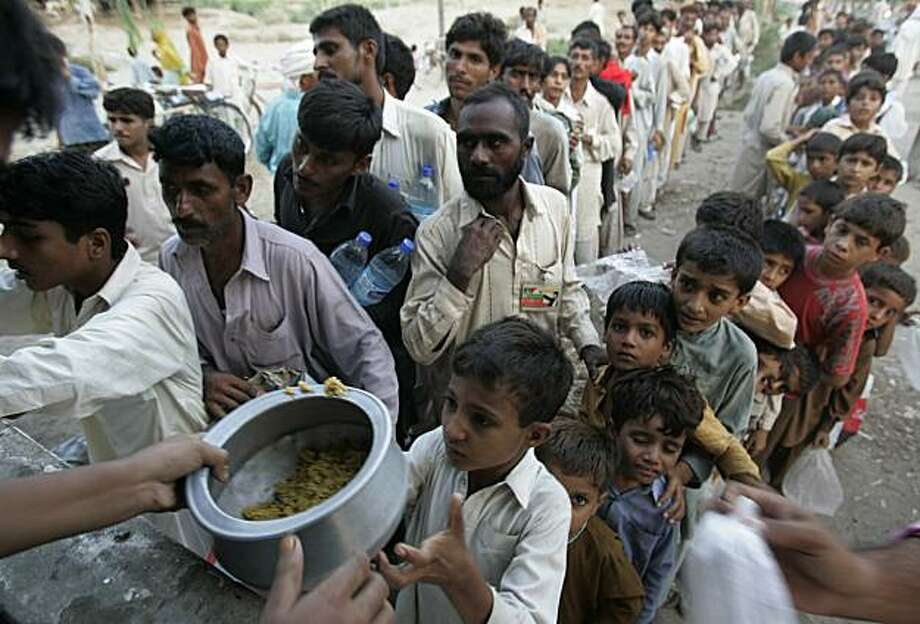 Pakistani flood affected children receive rice as they prepare to celebrate Eid, which ends the fasting month of Ramadan, at a camp setup for displaced people in Muzaffargarh district, Punjab province, Pakistan on Thursday, Sept. 9, 2010. Photo: Aaron Favila, AP