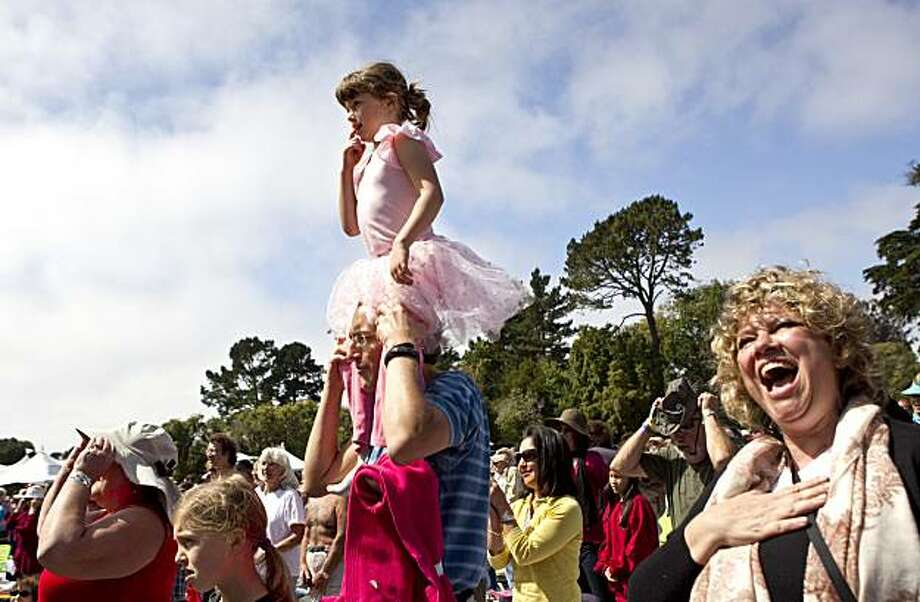 Savia Ronchetti, age 5, gets a better view on Francesco Ronchetti's shoulders as guests of Opera in the Park, including Veronique Damien-Nicolas (right) sing the Star Spangled Banner at the start of the event in Golden Gate Park in San Francisco, Calif. on Sunday, September 12, 2010. Photo: Laura Morton, Special To The Chronicle
