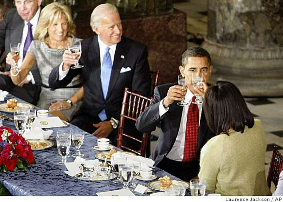 President Barack Obama, raises his glass for a toast with first lady Michelle Obama as Vice President Joe Biden and his wife Jill smile at the end  of their lunch at Statuary Hall in the U.S. Capitol  in Washington, Tuesday, Jan. 20, 2009. (Pool Photo/Lawrence Jackson, Pool) Photo: Lawrence Jackson, AP