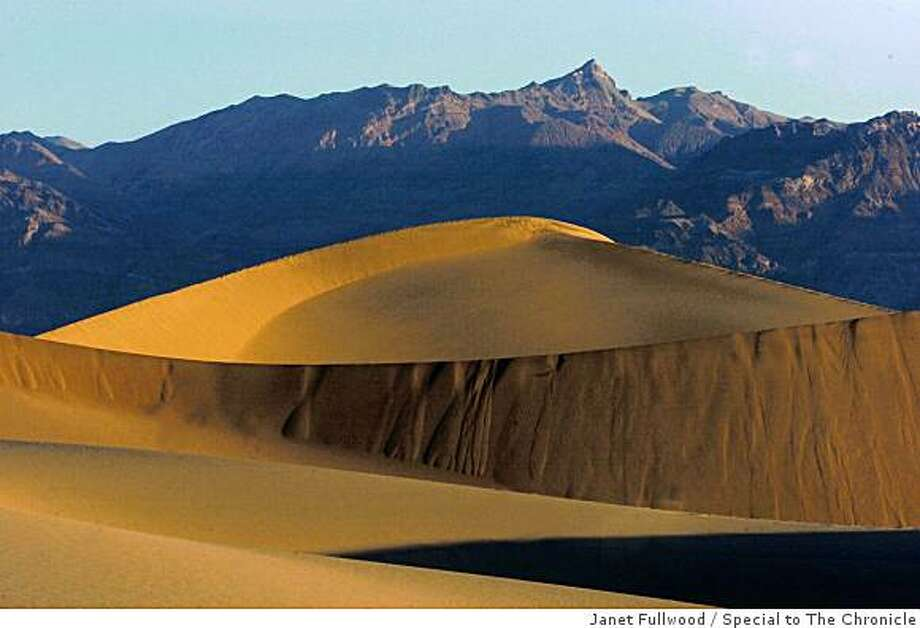 Wind-whipped shapes of sculpted sand stand before a panorama of the Funeral Mountains in Death Valley National Park. . Photo: Janet Fullwood, Special To The Chronicle