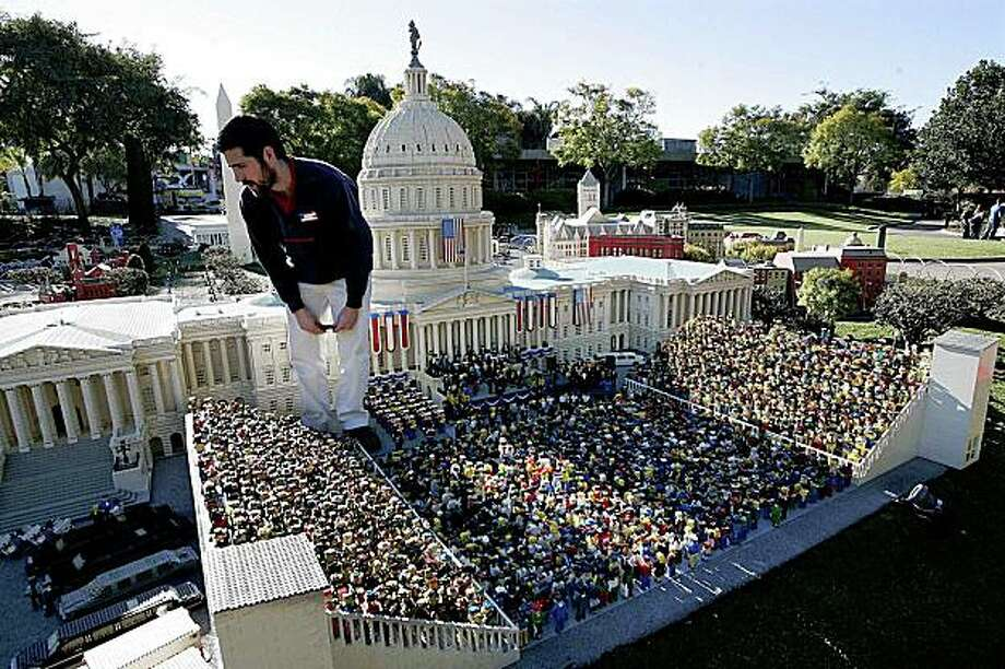This image provided by Legoland California shows a Legoland employee putting finishing touches on a Lego replica of President Barack Obama's presidential inauguration, on display at Legoland California on Thursday, Jan. 15, 2009 in Carlsbad, Calif. (AP Photo/Legoland, Sandy Huffaker) ** NO SALES ** Photo: Sandy Huffaker, AP