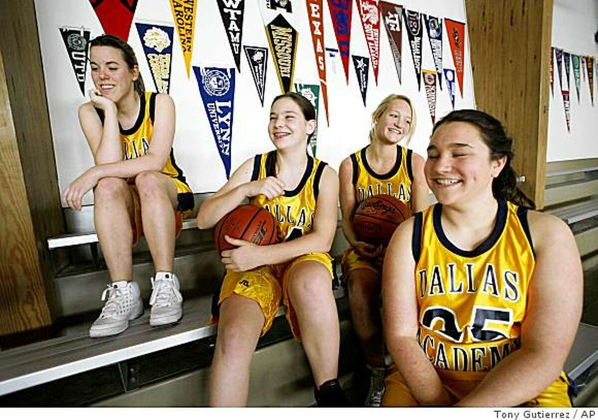 Dallas Academy basketball players Samantha Peloza, from left, Shelby Hyatt, Lauren Click and Eleanor Callan, right, smile as they respond to a question during an interview in their school gymnasium in Dallas, Thursday, Jan. 22, 2009. Covenant, a private Christian school in Dallas, defeated Dallas Academy 100-0 last week. The winning school now says it wants to do the right thing by seeking a forfeit and apologizing for the margin of victory. (AP Photo/Tony Gutierrez)