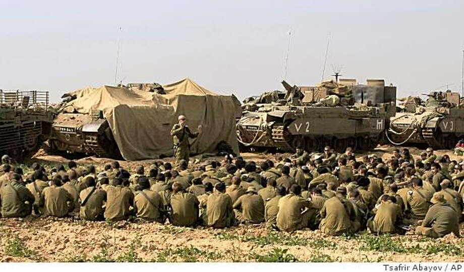 Israeli soldiers are briefed at a staging area  on the Israel-Gaza border,just outside the northern Gaza Stip, Wednesday Jan. 21, 2009. Israel withdrew the last of its troops from the Gaza Strip before dawn on Wednesday, the military said, as the government pursued diplomatic efforts to stanch the flow of arms into the Hamas-ruled territory. (AP Photo/Tsafrir Abayov) Photo: Tsafrir Abayov, AP