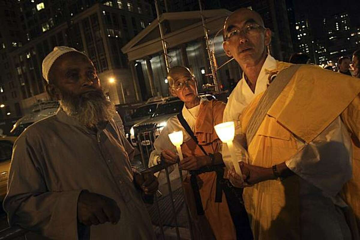 Mohamed Mostafa Kamal, left, and Buddhist monks Jun Yasuda, center, and Gyoju Ishivashi participate in a candle light vigil in support of the proposed Islamic cultural center two blocks from the World Trade Center site, Friday, Sept. 10, 2010 in New York.