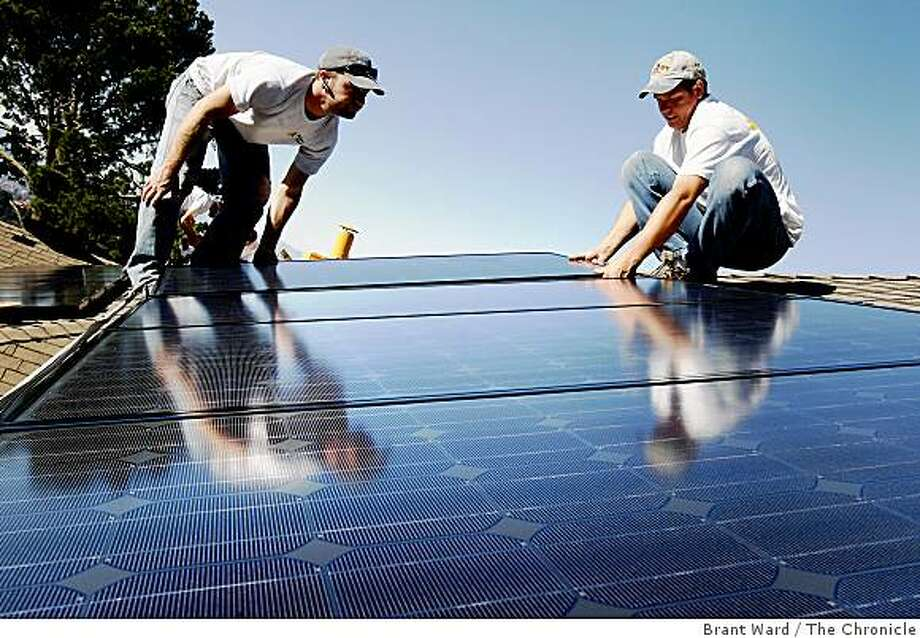 Solar installers Frank Teague, (left) and Delmar Oliveira positioned panels on the Oakland rooftop. The solar industry has been a bright spot in a down economy. The Los Gatos based company Akeena Solar is installing 44 solar panels on a home in the Oakland hills Thursday January 15, 2008. Photo: Brant Ward, The Chronicle