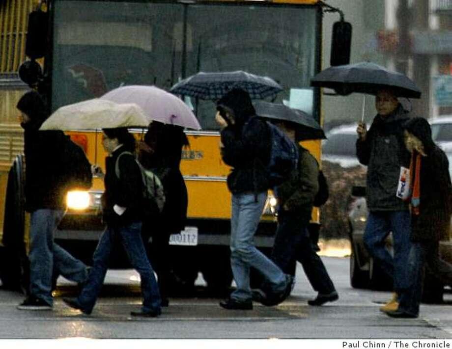 Pedestrians heading towards UC Berkeley carry umbrellas in the rain while crossing Shattuck Avenue in downtown Berkeley, Calif., on Thursday, Jan. 22, 2009. Photo: Paul Chinn, The Chronicle