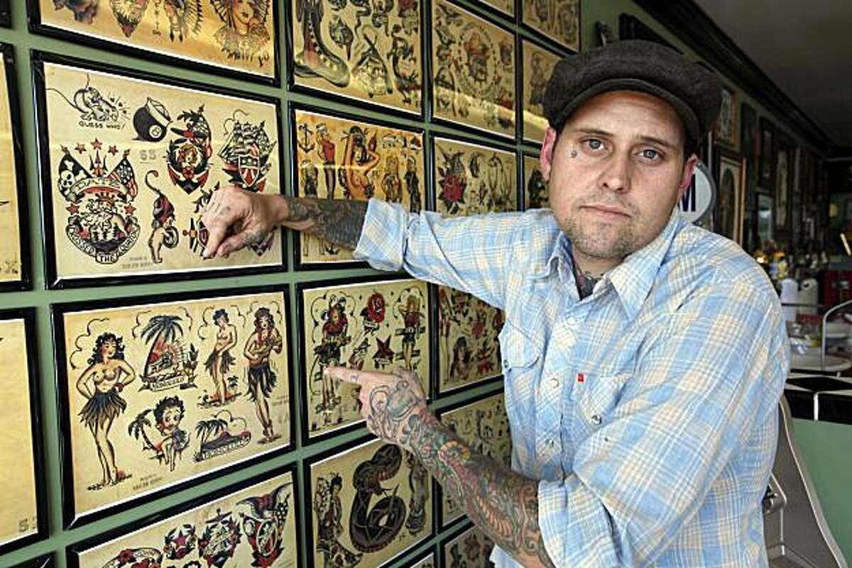 Lawsuit plaintiff, Johnny Anderson poses in front of a tattoo display at his Yer Cheat'n Heart Tattoo parlor in Gardena Calif., Thursday, Sept 9, 2010. A federal appeals court ruled Thursday that tattoos are artistic expressions entitled to full free speech protections in striking down a city's tattoo studio ban.