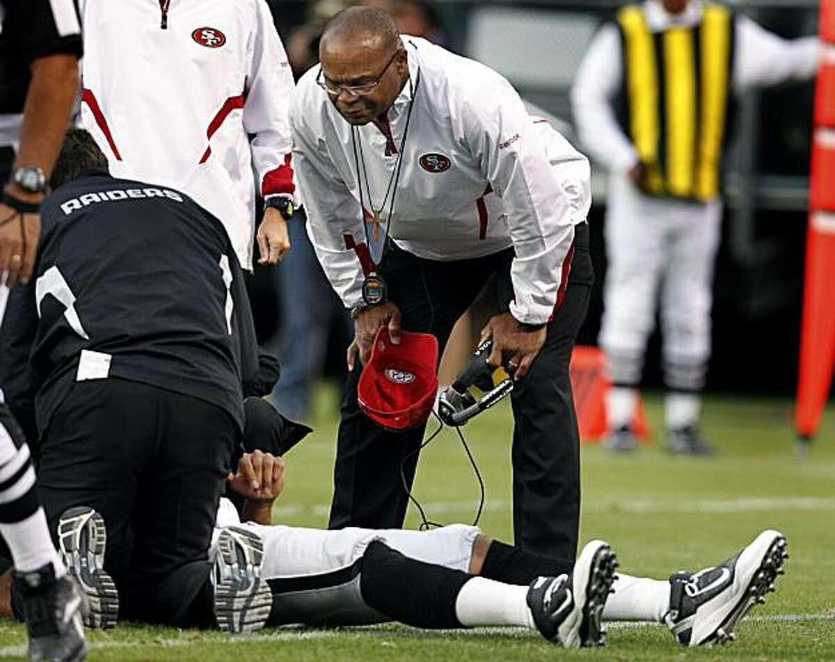San Francisco head coach Mike Singletary checks on Jason Campbell after the Raiderrs quarterback was injured on a sack in the second quarter in Oakland on Saturday.