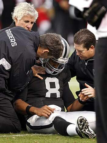 The training staff tends to Raiders quarterback Jason Campbell after a hard sack in the second quarter against the 49ers in Oakland on Saturday. Campbell was injured and left the game after the play. Photo: Paul Chinn, The Chronicle