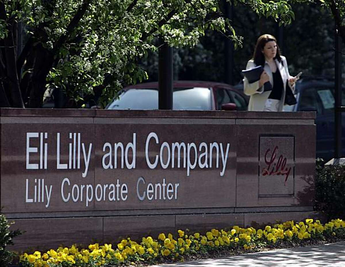 ** FILE ** In this April 18, 2006 file photo, a woman leaves the Eli Lilly and Company campus in downtown Indianapolis. Eli Lilly & Co. has agreed to spend more than $6 billion to fortify its cancer treatment portfolio by acquiring the biotechnology firm ImClone Systems Inc. in a deal that tops earlier offers from competitor Bristol-Myers Squibb Co. (AP Photo/Michael Conroy, file)