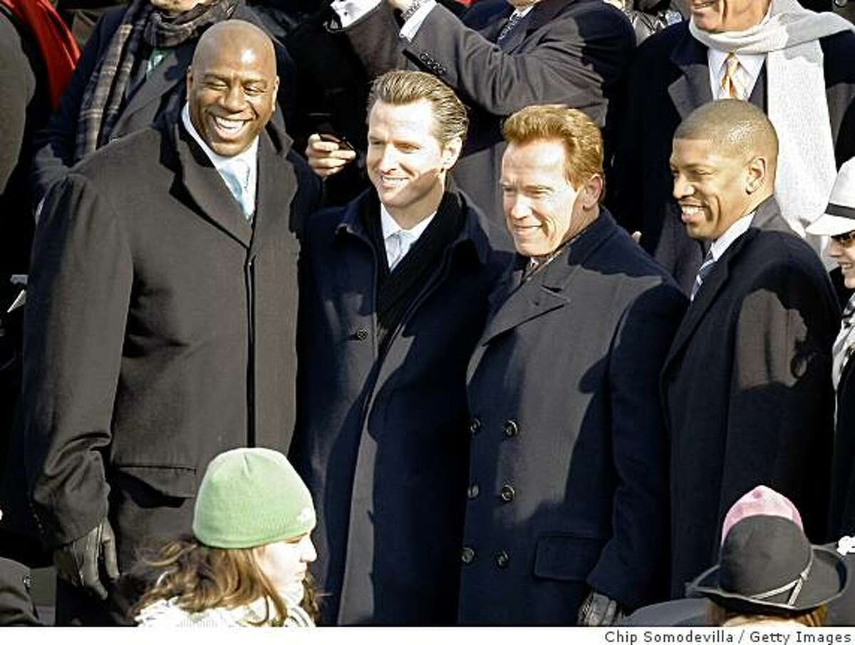 (L-R) Magic Johnson, San Francisco Mayor Gavin Newsom, California Arnold Schwarzenegger, and Sacramento Mayor Kevin Johnson stand on the inaugural stage ahead of the inauguration of Barack Obama as the 44th President of the United States of America on the West Front of the Capitol January 20, 2009 in Washington, DC. Obama becomes the first African-American to be elected to the office of President in the history of the United States. (Photo by Chip Somodevilla/Getty Images)