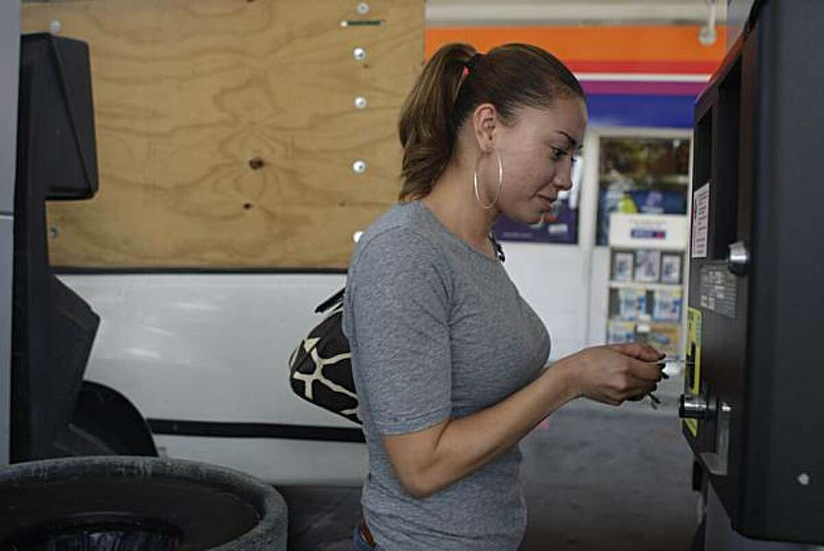 Eunice Iglesias of Richmond uses a debit card to pay for gas at an Arco in Albany, Calif. on Wednesday August 4, 2010. Lawmakers will consider a consumer protection measure that would ban stores from charging customers fees when they use a debit card.
