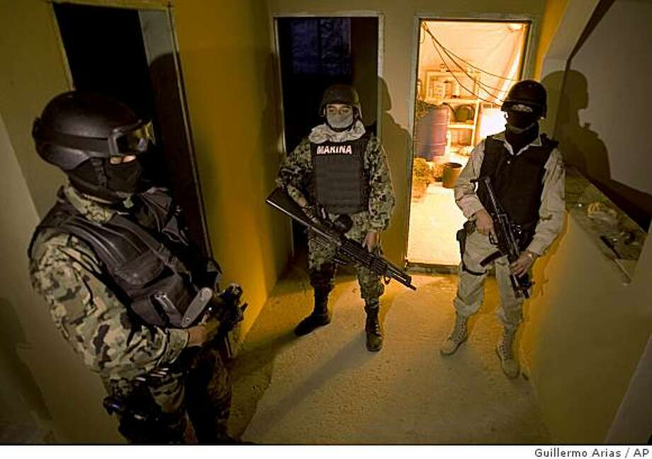 Mexican soldiers stand on guard in a house where marijuana plants being grown were found in Tijuana, Mexico, Thursday, Jan. 15, 2009.  Special forces soldiers found some 170 marijuana plants, in a room used as a greenhouse, and detained a suspect. (AP Photo/Guillermo Arias) Photo: Guillermo Arias, AP