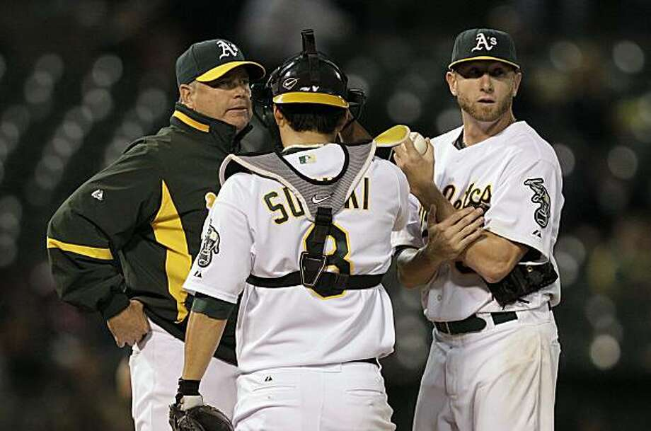 Oakland Athletics' Dallas Braden, right, receives a visit from pitching coach Curt Young during the second inning of a baseball game against the Seattle Mariners Tuesday, Sept. 7, 2010, in Oakland, Calif. At center is catcher Kurt Suzuki. Photo: Ben Margot, AP