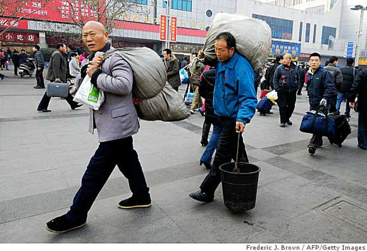 TO GO WITH CHINA-LUNAR-RAIL,FOCUS by Fran WangMigrant workers carry their luggage at the railway station in Zhengzhou, central China's biggest transport hub on January 17, 2009 in Henan province. Tens of millions of Chinese passengers are travelling by train for the annual Lunar New Year celebration, also known as Spring Festival, or Chunjie, the nation's most important holiday and a time for family get-togethers that this year falls on January 26. AFP PHOTO/Frederic J. BROWN (Photo credit should read FREDERIC J. BROWN/AFP/Getty Images)