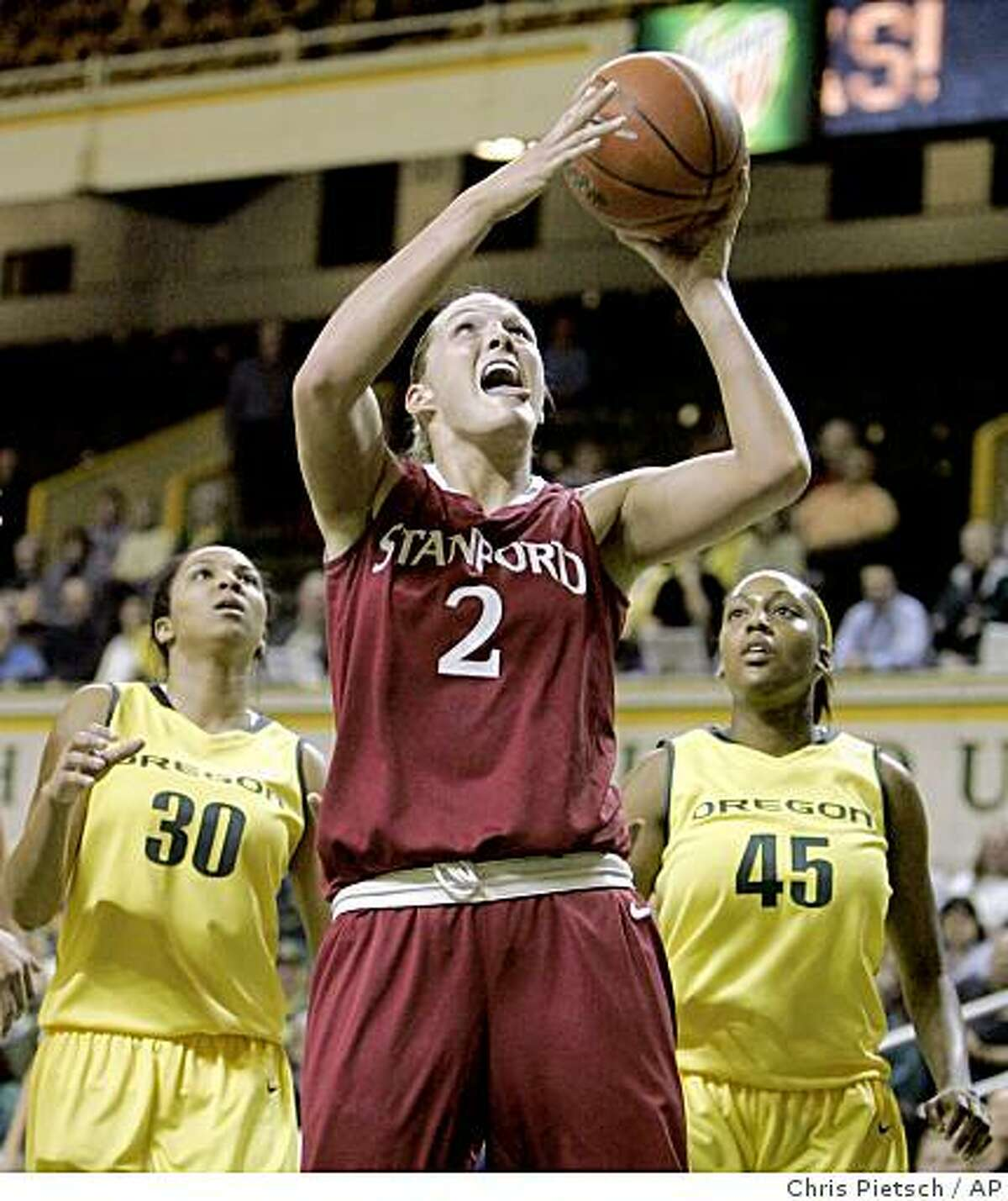 Stanford's Jayne Appel, center, shoots under the basket after slipping by Oregon's Jasmin Holliday, left, and Lindsey Saffold during the first half of an NCAA college basketball game in Eugene, Ore., Thursday, Jan. 22, 2009. (AP Photo/Chris Pietsch)
