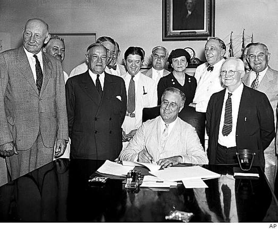 President Franklin Roosevelt signs the Social Security Bill in Washington on August 14, 1935.  The bill will provide old age pensions and unemployment insurance.  From left are: Chairman Doughton of the House Ways and Means Committree; Sen. Wagner, D-N.Y, co-author of the bill, Secretary Perkins, Chairman Harrison of the Senate Finance Committe, Rep. Lewis, D-Md., co-author of the measure. (AP Photo) Photo: AP