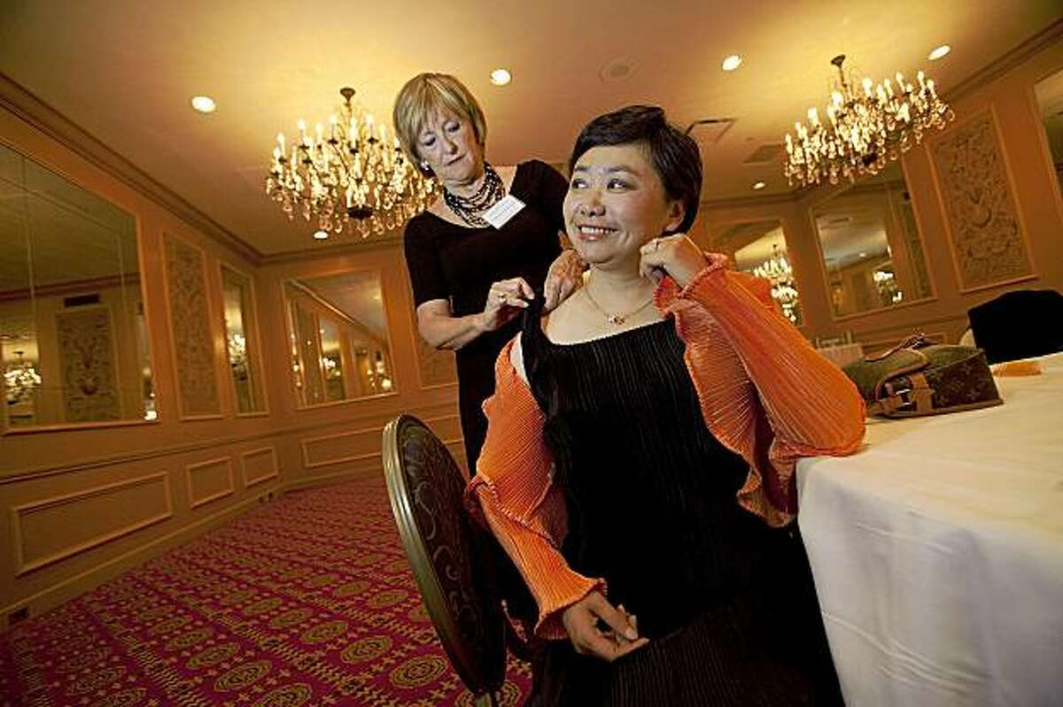 Zheng Cao, (R) a star with the San Francisco Opera has her dress mended by Frederica Von Stade (L) before singing at the opening night of the International Lung Cancer Conference gala at the Fairmont Hotel July 29, 2009 in San Francisco, Calif. (Photograph by David Paul Morris Special to the Chronicle)