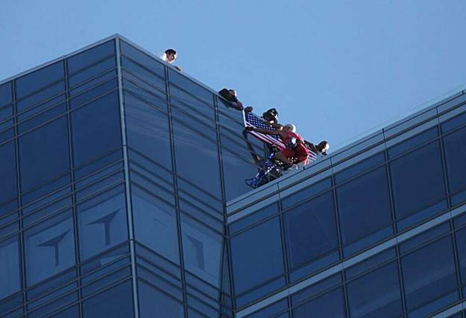 San Francisco Fire Department officials help Dan Goodwin, aka Spider Dan, as he hangs an American flag at the top of the Millennium Tower on Mission Street on Monday Sept. 6, 2010 in San Francisco. Goodwin used suction cups but no ropes to scale the 645-foot residential building overlooking San Francisco Bay. Police say he ignored orders to stop climbing. Photo: Mike Kepka, AP