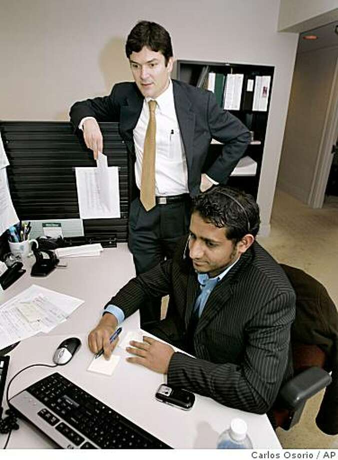 University Bank President and Chairman Stephen Lange Ranzini, standing, talks with banking consultant Nabeel Shahid at the bank in Ann Arbor, Mich., Thursday, Nov. 20, 2008. (AP Photo/Carlos Osorio) Photo: Carlos Osorio, AP