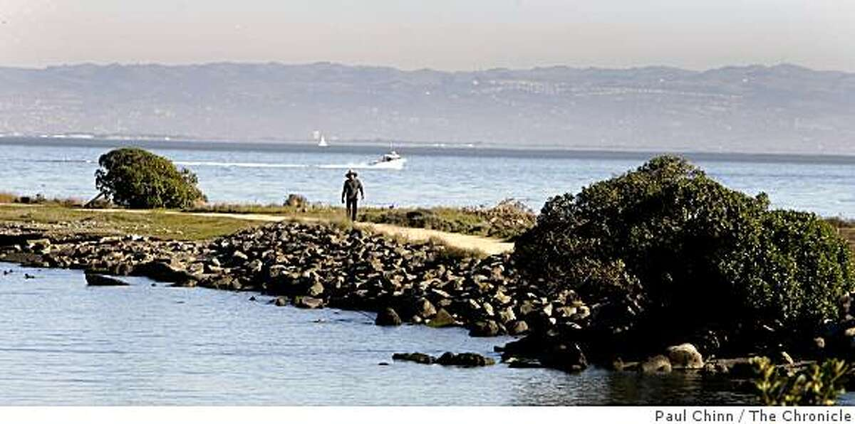 A man walks on a trail at the end of Heron's Head Park in San Francisco, Calif.