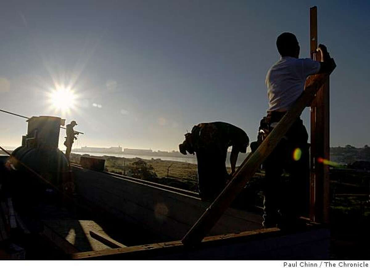 The sun rises behind workers building the EcoCenter at Heron's Head Park. Construction of the environmentally-conscious interpretive center, slated to open in April, may be stalled because of the ongoing state budget crisis.