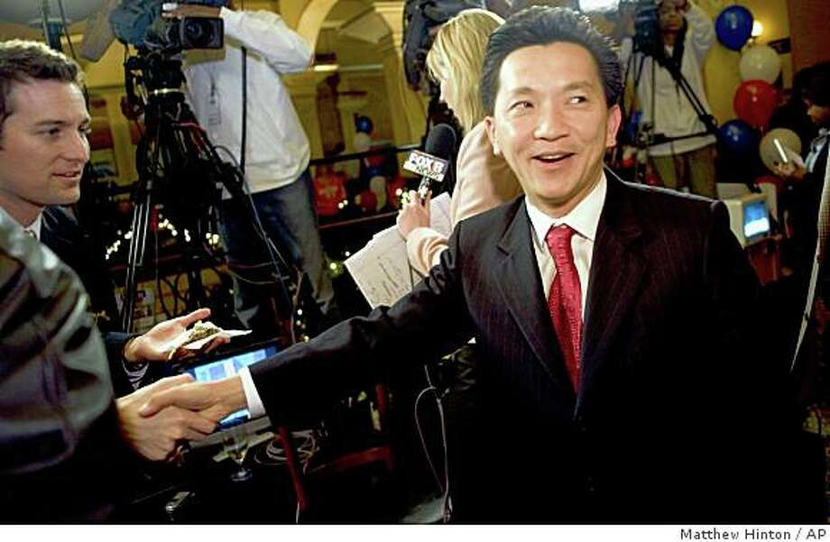 "Anh ""Joseph"" Cao, right, is greeted by a reporter at the Palace Cafe in New Orleans. He ousted U.S. House District 2 incumbent William Jefferson Saturday Dec. 6, 2008. Photo: Matthew Hinton, AP"