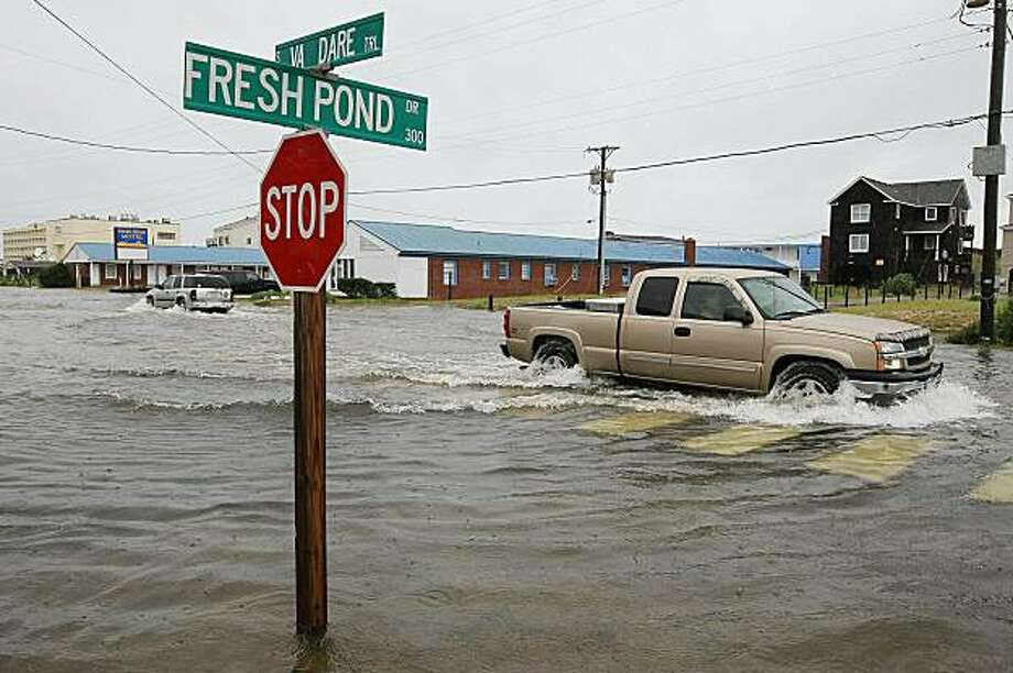 KILL DEVIL HILLS, NC -SEPTEMBER 03: Cars drive on a flooded beach road on September 3, 2010 in Kill Devil Hills, North Carolina. Hurricane Earl was downgraded to a category 2 before brushing the Outer Banks early Friday morning causing minimal damage. Photo: Mark Wilson, Getty Images