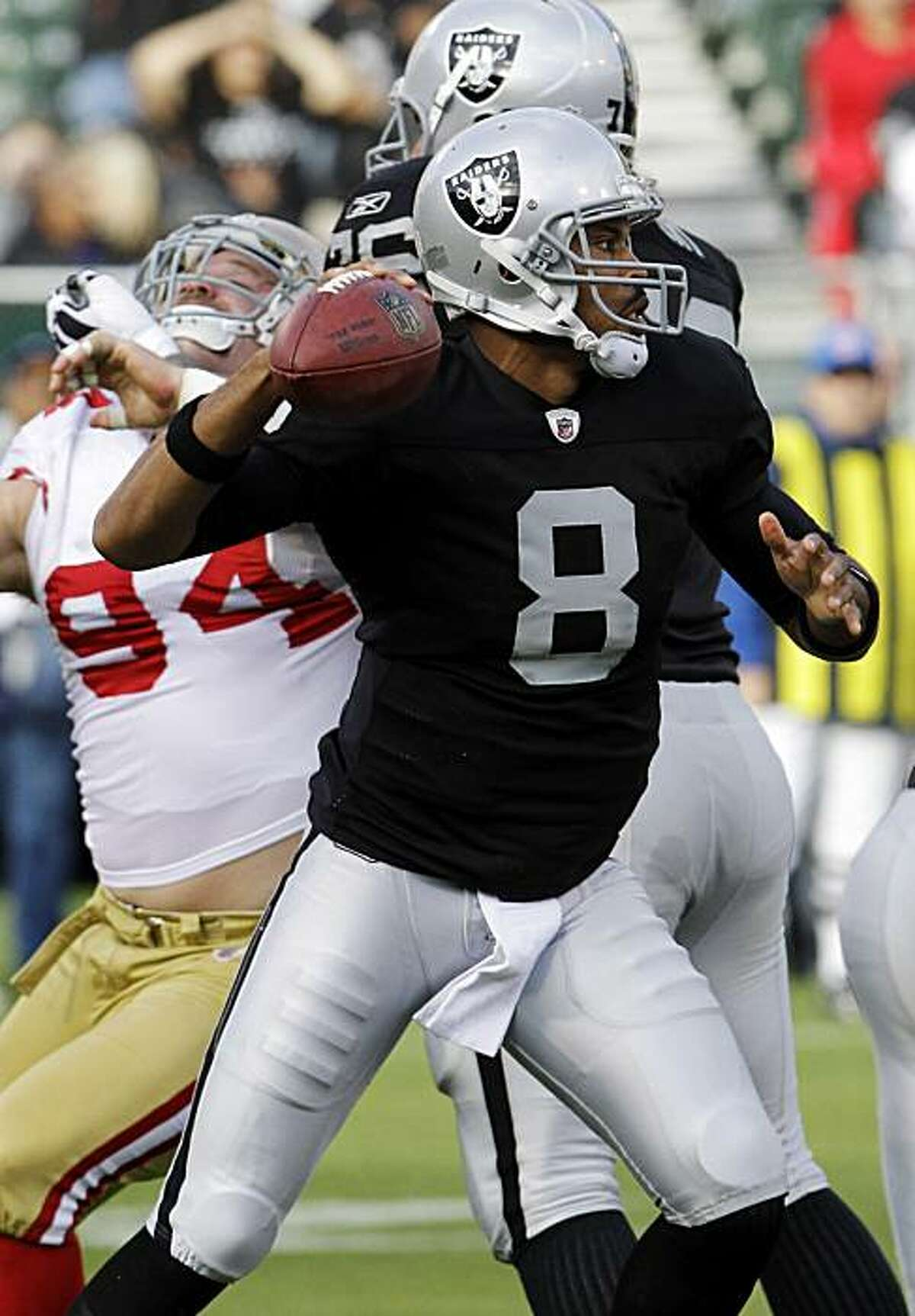 Oakland Raiders quarterback Jason Campbell (8) throws under pressure from San Francisco 49ers defensive tackle Justin Smith, left, during the first half of a preseason NFL football game in Oakland, Calif., Saturday, Aug. 28, 2010.